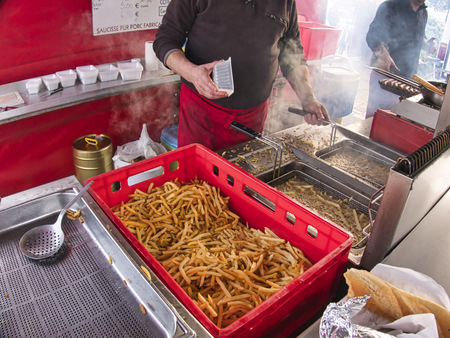 French fries cooking. Grid with strips of potato lowered into boiling oil. The concept of fast food, delicious food, outdoor stand restaurant