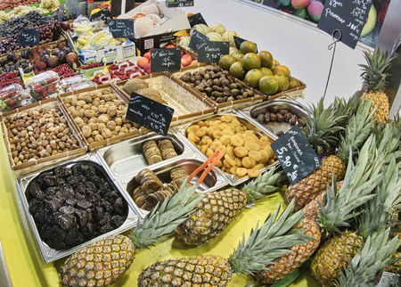 St Vaast, France - December circa, 2018. Exotic fruits. Market stall with variety of organic fruits. Colorful fruits in the marketplace. Bright summer background. Healthy, organic food. Natural nutrition for diet.