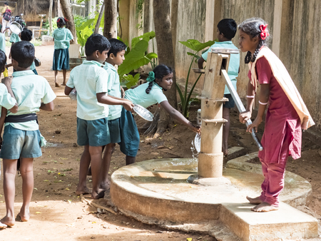 PUDUCHERRY, TAMIL NADU, INDIA - DECEMBER Circa, 2018. Unidentified poor classmates children with uniforms queueing outdoors to clean their plate at the well before eating. Lunch time, unhealthy food in public government school