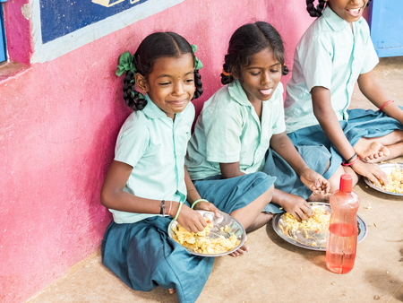 PUDUCHERRY, TAMIL NADU, INDIA - DECEMBER Circa, 2018. Unidentified poor classmates girls with uniforms sitting on the floor outdoors, eating with their right hand some rice with masala. Lunch time, unhealthy food in public government school