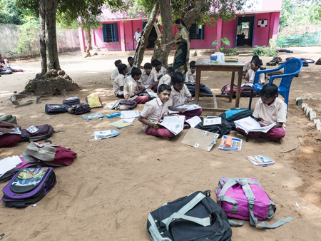 PUDUCHERRY, INDIA - DECEMBER Circa, 2018. Unidentified group children girls friends classmates in government school uniforms sitting on floor, studying with books outdoors. With lot of school bags