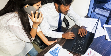 Two young adult man woman indian working together on desk with graphs sheets, mobile and laptop. Team work with colleagues, brainstorming. Man sitting woman standing up phoning talking. Stock Photo