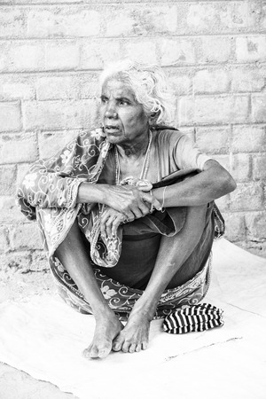 PUDUCHERRY, INDIA - DECEMBER Circa, 2018. Unidentified portrait of old face indian woman sitting outdoor in village, very serious. Black and white image