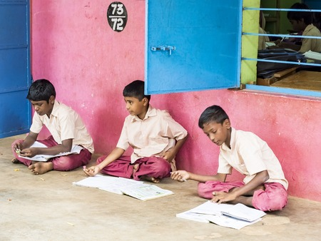 PUDUCHERRY, INDIA - DECEMBER Circa, 2018. Unidentified happy concentrated boys classmates in government school uniforms sitting on floor, studying with books outdoors. Portrait of school teenagers enjoying friendship emotion.