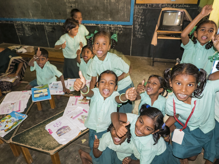 PUDUCHERRY, INDIA - DECEMBER Circa, 2018. Unidentified happy classmates in government school uniforms sitting on floor, studying reading books indoors classroom. Portrait of school teenagers enjoying friendship emotion. Stock Photo - 120377356