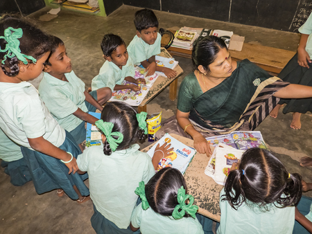 PUDUCHERRY, INDIA - DECEMBER Circa, 2018. Unidentified happy classmates in government school uniforms sitting on floor, studying reading books indoors classroom with teacher. Portrait of school teenagers enjoying friendship emotion.