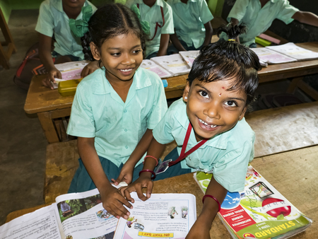 PUDUCHERRY, INDIA - DECEMBER Circa, 2018. Unidentified happy pupils classmates in government school uniforms studying reading english books indoors classroom. Portrait of school poor teenagers smiling for ngo help