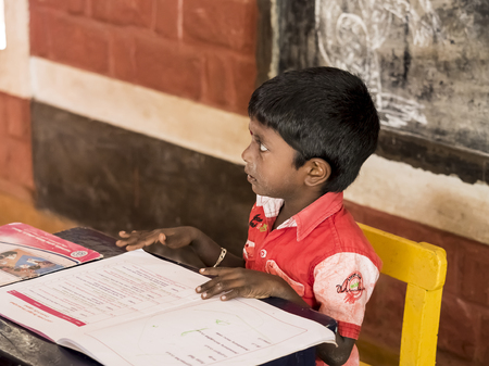 PUDUCHERY, INDIA - DECEMBER Circa, 2018. Unidentified cute beautiful poor concentrated kid reading a book in the creche