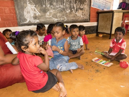 PUDUCHERY, INDIA - DECEMBER Circa, 2018. Interior of poor kids playing room creche with unidentified cute children, playing entertainment, recreation, sports, educational wooden games indoor
