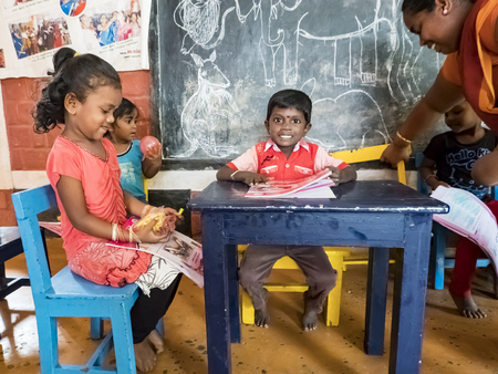 PUDUCHERY, INDIA - DECEMBER Circa, 2018. Poor preschool teacher and her group of kids boys girls having some fun at school with just a few wood toys games. Poverty at school