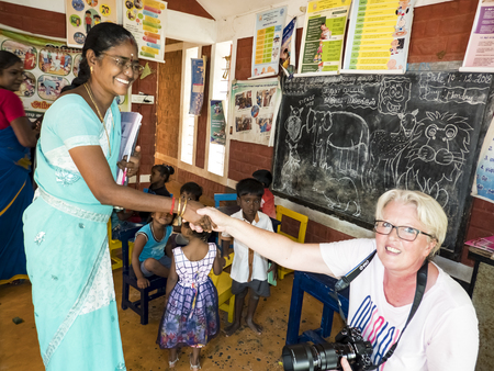 PUDUCHERY, INDIA - DECEMBER Circa, 2018. Two unidentified beautiful caucasian indian women shaking hands and looking at camera with smile to thanks for ngo help for government preschool