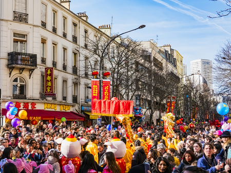 PARIS, FRANCE - FEBRUARY 17, 2019. Last day of the chinese new year celebration festival in street. People dragon lion dancing show colorful costumes. 200 thousands, multi ethnic asian man woman. Year of pig