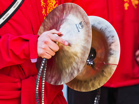 PARIS, FRANCE - FEBRUARY 17, 2019. Last day of the chinese new year celebration festival. Musician playing cymbal in the street during the parade festival. Traditional celebration and costumes.