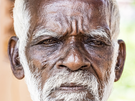 PUDUCHERY, INDIA - DECEMBER Circa, 2018. An unidentifed old senior indian poor man portrait with a dark brown wrinkled face and white hair and a white beard, looks serious. Emotional picture