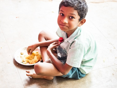 PUDUCHERY, INDIA - DECEMBER Circa, 2018. Portrait of unidentified handsome cute smiling indian boy outdoors, eating plate of rice. Concept of joyful even if they are poor people.