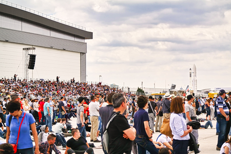 LE BOURGET, FRANCE - JUNE 24, 2017. Aircrafts parked at meeting space in Paris Le Bourget during the Aeronautics and spatial international airshow and aviation exhibition, with crowd peole looking airforce flight.