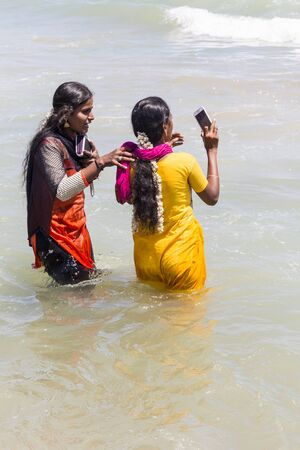 MASI MAGAM FESTIVAL, PUDUCHERY, PONDICHERY, TAMIL NADU, INDIA - March 1, 2018. Unidentified Indian pilgrims women with colored Sari bathing in the sea, on the beach