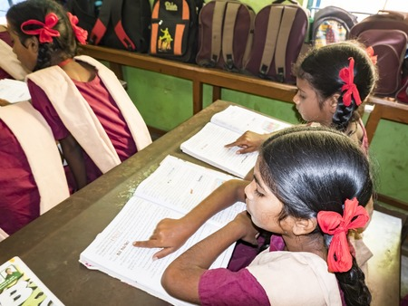 PUDUCHERRY, INDIA - DECEMBER Circa, 2018. Unidentified concentrated serious classmates in government school uniforms sitting on chair, studying reading books indoors classroom. Portrait of school teenagers
