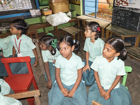 PUDUCHERRY, INDIA - DECEMBER Circa, 2018. Unidentified happy pupils classmates in government school uniforms sitting, studying indoors classroom. Portrait of school poor teenagers smiling for ngo help. Editorial