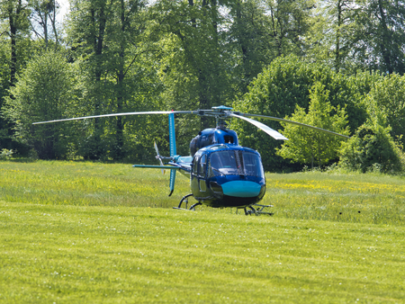 helicopter standing on green grass field, waiting for pilot