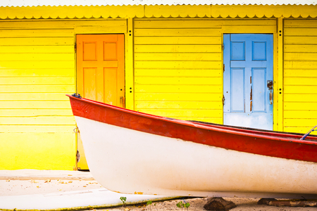 Beautiful bright colored yellow orange blue wooden house on beach with colorful wooden with and red boat in front. Caribbean place, travel concept