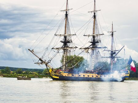 RIVES EN SEINE, FRANCE - June 5, 2019. Hermione sailing french very old boat on the river Seine, just arriving for the Armada 2019, to go to Rouen. With firecracker and smoke for parade. With unidentified people dressed with pirate clothes. Publikacyjne
