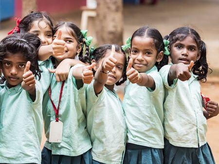 PUDUCHERRY, INDIA - DECEMBER Circa, 2018. Unidentified happy best children boys girls friends classmates in government school uniforms smiling showing thumb up gesture. Portrait of school childs enjoying friendship emotion.