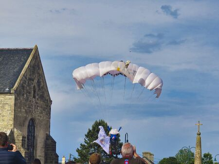SAINTE MERE, NORMANDY, FRANCE - JUNE 06, 2019. D Day 75 birthday of french liberation by allied countries. Ceremony to remind what american, british, canadian soldiers did during world war two. Parachutist jumping near church with french flag