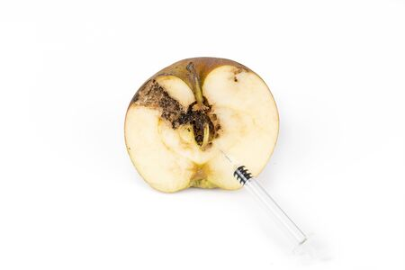Close-up Boring trace of a codling moth Cydia Pomonella, in a half wormy apple. On white background. With syringe needle. Concept non organic food and genetically modified organism. Place to write Stock Photo
