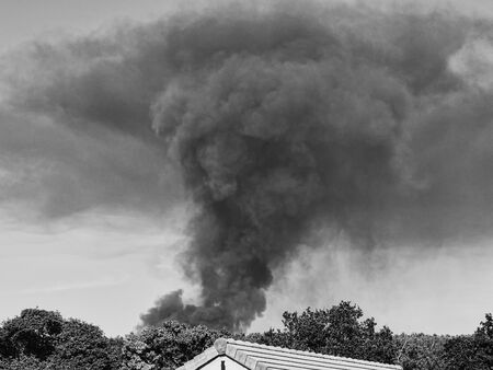 A Burning plastic recycling place causes a big pile of dark, black thick smoke on a sky blue summer day. Danger, sorrow. Terrorist attack or explosion. Environmental disaster