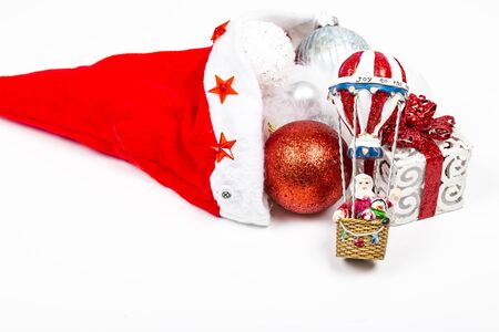 Santa Claus hat cap with Christmas presents and balls ornaments on white background
