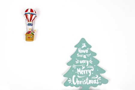 Santa Claus in Hot air balloon flight up to a wood green tree with Merry Christmas written on, on white background. Place to write
