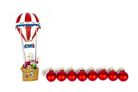 Santa Claus in Hot air balloon flight with red balls decoration on white background. Place to write