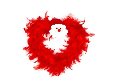 Red Heart Christmas Decoration made with red feather, with Santa Claus head in the middle, on white background