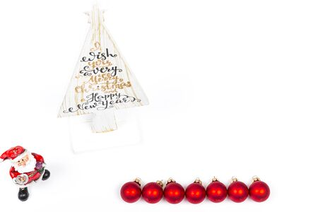 Beautiful Minimal Christmas wood white tree with Merry Christmass and happy new year written, with small Santa Claus and red balls, on white backgound.