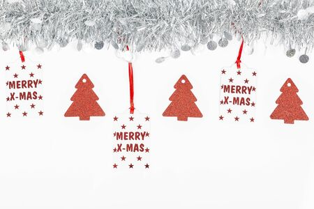 Christmas silver grey garland photo with Merry Christmas label written in red and red trees paper on white background.