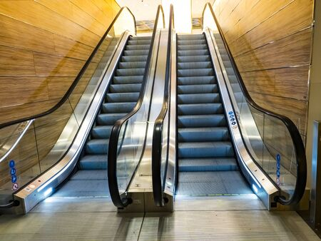 Escalator at an airport with no people. Symmetrical architecture interior design. Modern, sleek interior design with metal and reflective surfaces. Gold light
