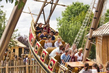 LE BOCASSE, FRANCE - AUGUST CIRCA, 2019. Unidentiofied children teenagers and adults in Carousel boat rolling at amusement park.