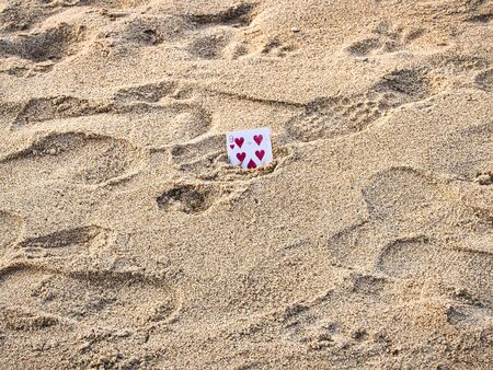 Poker playing cards buried in a sand dune, India