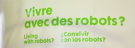Green Text on white sign showing Living with robots in english, french and spanish. Banner size