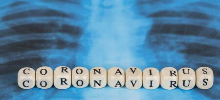 Novel Covid-19, virus concept. Text phrase Coronavirus with wooden letter on lungs radiology blue image background. Copy space. Panoramic banner size