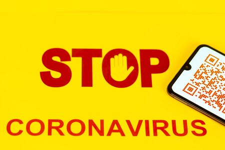 STOP Sign with red colorful QR Code on smart phone screen for coronavirus Covid-19 infection used in company for workers to know about their health virus infection. Yellow background. New way against epidemic virus in the world