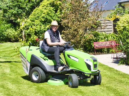 Senior man 75 old years driving a tractor lawn mower in garden with flowers. Green and white ride on mower, turning in field between colorful flowers Imagens