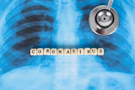 Text phrase Coronavirus with wooden letter on lungs radiology blue image background, with stethoscope. Copy space