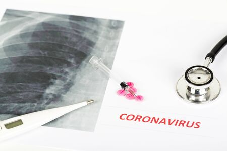 Text phrase Coronavirus with red letters close to lungs radiology x-ray image on white background. Copy space. With pills, syringe vaccine, thermometer and stethoscope. Panoramic size Imagens - 145215853