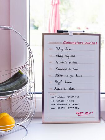weekly planning sign with stay at home in different languages for each day, indoors in kitchen, on window with orange fruits and vegetables. Sun is shining