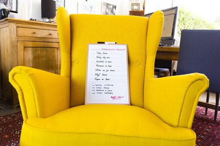 weekly planning sign with stay at home in different languages for each day, indoors in yellow armchair in the living room.