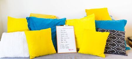 weekly planning sign with stay at home in different languages for each day, indoors on grey sofa with yellow and blue cushions, pillows in the living room, with white wall.