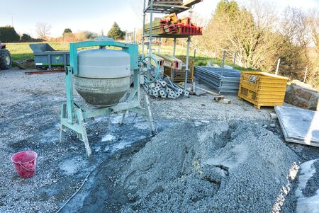 Cement machine close to bunch of gravel stones with red bucket of water. Construction working