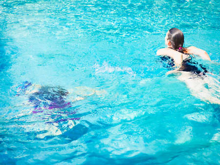 Cheerful mature woman relaxing in swimming-pool in crystal water with summer light